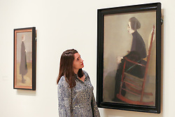 "© Licensed to London News Pictures. 17/07/2019. London, UK. A staff member views Helene Schjerfbeck's painting ""The Seamstree (The Working Woman) 1905"" at Royal Academy of Arts during the preview of her first ever exhibition in the UK. The exhibition features around 65 portraits, landscapes and still life, charting the development of Helene Schjerfbeck's work from a naturalistic style inspired by French Salon painters in the early 1880s, to a radically abstracted and modern approach from the turn of the twentieth century onwards. The exhibition runs  from 20 July to 27 October 2019. Photo credit: Dinendra Haria/LNP"