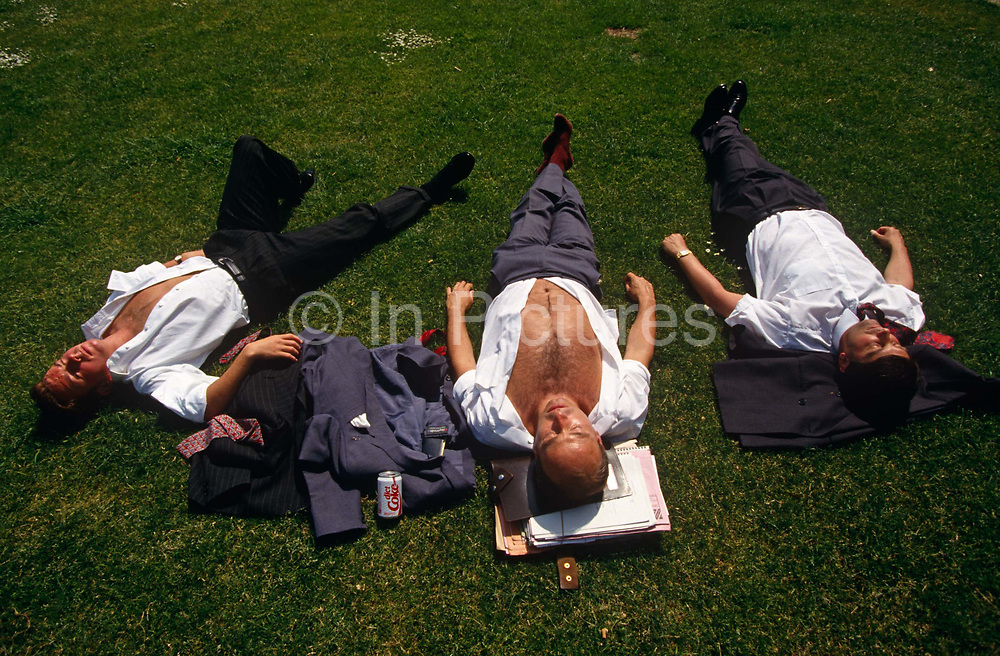 Looking down from above, we see young men who are open-chested and with their suit jackets either beneath their heads or on the grass, three office co-workers stretch out over the lush grass and sunbathe during a hot summer lunchtime in Trinity Square in the City of London, England. One has his paperwork under his head and a can of Coke to quench his thirst. Already tanned, the threesome bask under a hot mid-day sun. Risking sunburn after prolonged solar radiation exposure, they enjoy the inner-city heatwave.