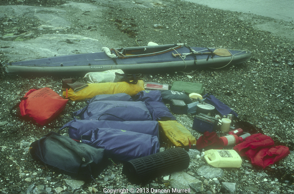 """Duncan Murrell's Klepper Aerius 1 folding kayak and gear at the start of a kayaking trip, Angoon, Admiralty Island, Southeast Alaska, USA.<br /> <br /> My partner and I eventually separated and I had one last fantastic summer alone cruising around Southeast Alaska with """"Avalon"""" and my Klepper folding kayak. After that I just used my kayak and took everything that I needed to travel around with the humpback whales and camp out for many weeks alone in the Alaskan wilderness. It became a big challenge to be able to pack so much food and equipment in drybags into and onto my small folding kayak; everything had its place in the intricate jigsaw puzzle. Packing the kayak was always a chore but a necessary one to enable me to have so much freedom all summer. I developed a good system for taking the right dried food along with a certain amount of fresh food that could be hung up in the trees and eaten in the right order. That was supplemented with a growing knowledge of wild food that could be harvested from the beaches and the forest."""