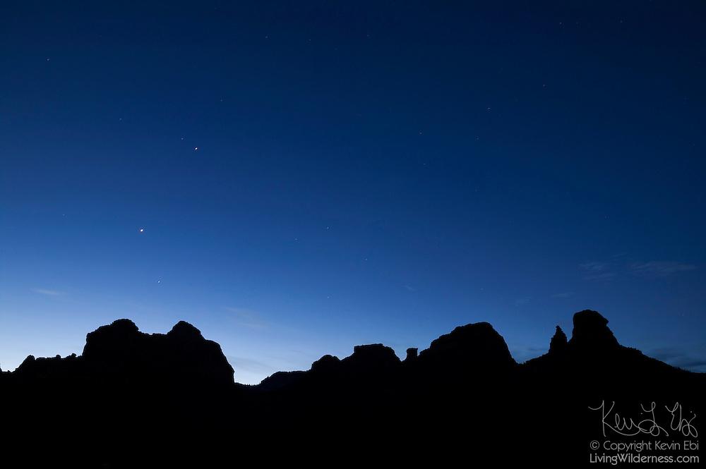 A few stars shine above Mitten Ridge, which is rendered in silhouette just before sunrise near Sedona, Arizona.