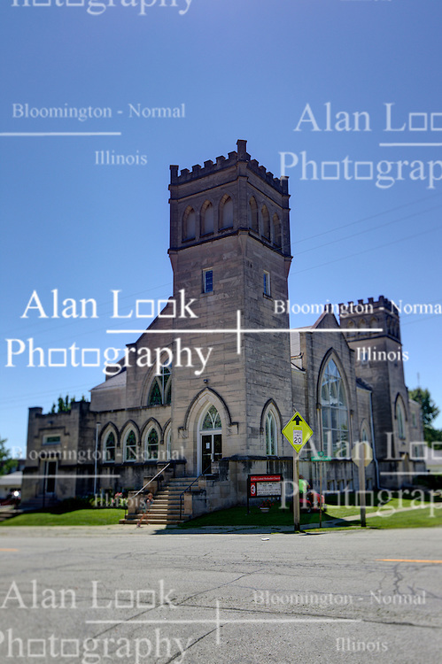 31 July 2015:   A stone gothic style church with arched stained glass windows, doorway and a belfry is occupied by the Colfax United Methodist church in Colfax Illinois<br /> <br /> <br /> This image was produced in part utilizing High Dynamic Range (HDR) processes.  It should not be used editorially without being listed as an illustration or with a disclaimer.  It may or may not be an accurate representation of the scene as originally photographed and the finished image is the creation of the photographer.
