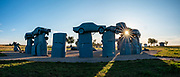 """A sunburst shines through Carhenge at sunset. Carhenge replicates England's Stonehenge using vintage American automobiles, near Alliance, Nebraska, in the High Plains region, USA. After studying Stonehenge in England, years later, Jim Reinders recreated the physical size and placement of Stonehenge's standing stones in summer 1987, helped by 35 family members. Reinders said, """"It took a lot of blood, sweat, and beers."""" Carhenge was built as a memorial to Reinders' father. 39 automobiles were arranged in the same proportions as Stonehenge with the circle measuring a slightly smaller 96 feet (29m) in diameter. Some autos are held upright in pits five feet deep, trunk end down, while other cars are placed to form the arches and welded in place. All are covered with gray spray paint. The heel stone is a 1962 Cadillac. Reinders donated Carhenge to the Friends of Carhenge, who gifted it to the Citizens of Alliance in 2013.  This image was stitched from multiple overlapping photos."""