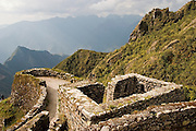 Sunset light illuminates the Inca ruins of Phuyupatamarca along the Inca Trail to Machu Picchu, Peru.
