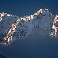 Mount Kangtega towers above clouds in the Khumbu Region in Nepal.