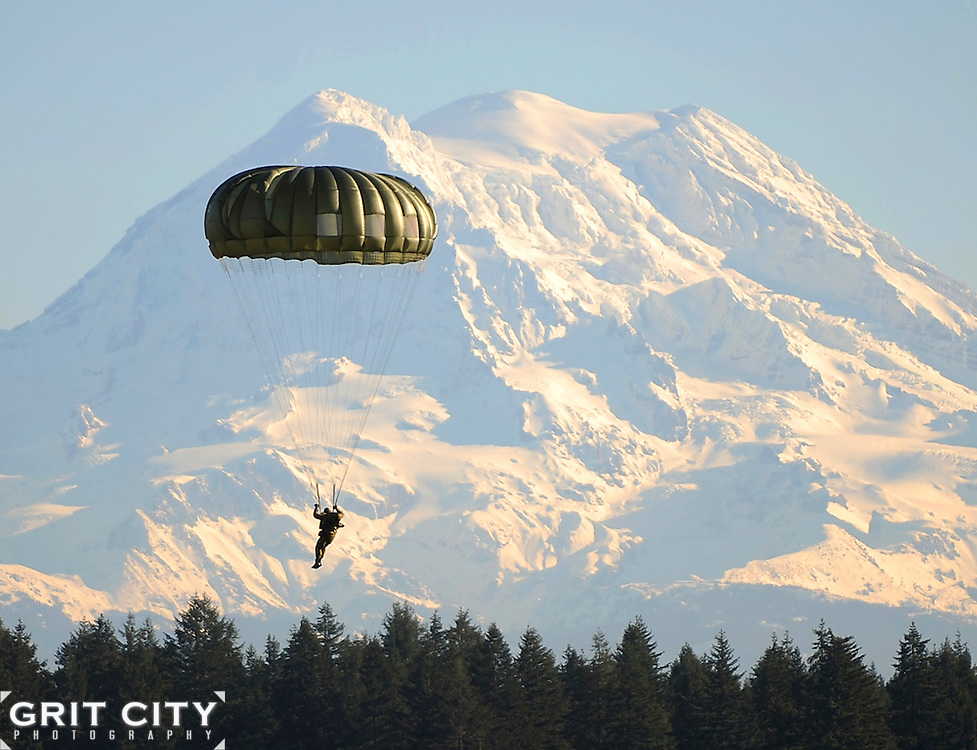 A Canadian Special Operations Soldier descends in front of Mt. Rainier onto the Rogers Drop Zone after jumping with U.S. 1st SFG Soldiers from a Chinook helicopter Dec. 2 during Menton Week. The week-long celebration leads up to the 65th annual Menton Day, which commemorates the inactivation of the combined U.S. and Canadian First Special Service Force on Dec 5, 1944.
