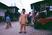 Boy with toy gun in neighborhood of Kuala Lumpur near the Petronas Towers.