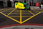 Bright yellow and green City Link delivery van drives mid-way over a yellow box junction grid in a City of London street. City Link are one of the largest national networks operating from over 70 Depots across the UK with a further 17 Depots in Ireland. City Link offer next day deliveries and have 6 regional hubs based in Coventry, Bristol, Heathrow, Warrington, Peterborough and Glasgow.