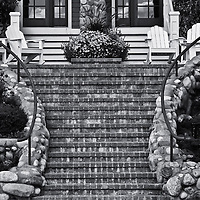 """""""The Setting""""<br /> <br /> This image is a black and white semi-symmetrical view of lovely set of  stairs, a porch and a sitting area in the quiet town of Bay Harbor!<br /> <br /> Black and White Images by Rachel Cohen"""