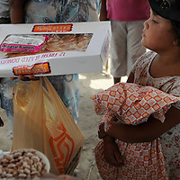 Aug 10, 2010 - Matamoros, Mexico - A young girl stands behind her mother in line at a make shift distribution point  in the Colonia of Leyes De La Reforma near the city dump of Matamoros Mexico to collect bread, rice,beans, pastries and on Tuesday some school supplies from the Frank Ferree Border Relief group. An Organization which was started by Frank Ferree a former World War I soldier who moved to the Rio Grande Valley in Texas to farm citrus, but ended up devoting his life to helping the poor across the border from his home in Harlingen Texas. Ferree received a Presidential Medal of Freedom from the Former President Reagan and was nominated for a Nobel Peace Prize. .(Credit Image: © Josh Bachman/ZUMA Press)
