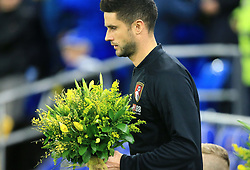 Bournemouth's captain Andrew Surman walks out with a bouquet of flowers in memory of Emiliano Sala during the Premier League match at the Cardiff City Stadium.