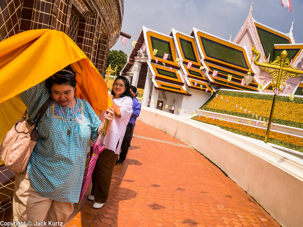 12 OCTOBER 2012 - NAKHON PATHOM, NAKHON PATHOM, THAILAND:  Thai Buddhists wrap Phra Pathom Chedi with blessed cloth in a traditional merit making ceremony in Nakhon Pathom. The Phra Pathom Chedi in Nakhon Pathom was commissioned by King Mongkut and completed by King Chulalongkorn in 1870. The chedi is 127 meters tall and is one of the tallest pagodas in the world. It is located in the center of the city of Nakhon Pathom and has been an important Buddhist center since the 6th century. According to local history, Nakhon Pathom is where Buddhism first came to Thailand.     PHOTO BY JACK KURTZ