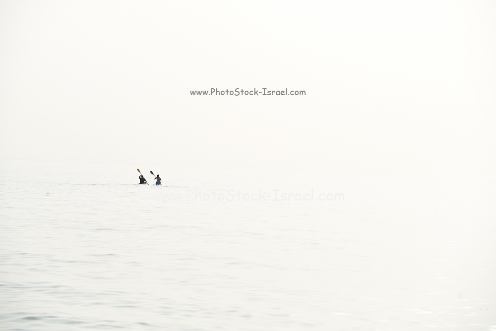 high key image of two distant figures rowing in the ocean