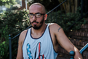 """BIRMINGHAM, AL – SEPTEMBER 4, 2020: Jonathan Perez, 31, stands outside his home in Hoover.<br /> <br /> As the coronavirus pandemic continues to grow in the United States, the cost of recovery from Covid-19 has varied considerably for Americans. Jonathan Perez, 31, contracted Covid-19 and was admitted to a nearby hospital in Birmingham, where his condition quickly worsened. """"They didn't think I'd make it,"""" Perez said. """"I'd said my peace."""" Fortunately Perez recovered, but he'd incurred medical bills in excess of $50,000. The uninsured Marine veteran was told his entire bill would be covered by the hospital using funds from the CARES Act. In the end, he ended up paying around $800. Perez, who has been virus-free for about a month, still suffers from fatigue. He spends his time trying to recover full use of his lungs by walking his dogs several times a day. """"I'm just thankful to be here,"""" he told me."""