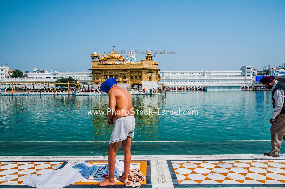 Sikh pilgrims drying off after bathing in the sacred tank surrounding the Golden Temple in Amritsar, India