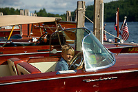 "CJ Spoler sits at the helm of his grandfather's 1956 Century Coranado ""Amazing Grace"" during the Antique Boat Show in Alton Bay Saturday morning.  (Karen Bobotas/for the Laconia Daily Sun)"