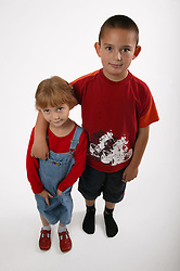 Young boy with his arm around his sister,