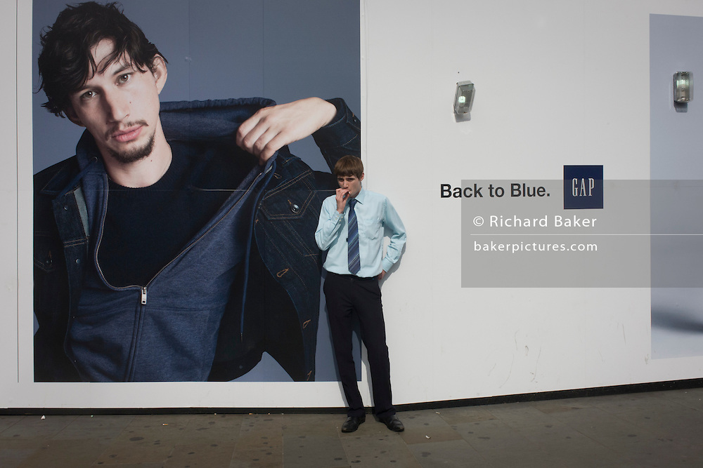 A young man stops to smoke a cigarette in front of a hoarding for the clothing retailer Gap, in central London.