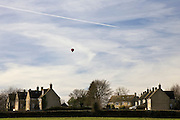 Hot air balloon flies over village of Little Rissington, Gloucestershire, United Kingdom