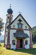 The Baroque, onion-domed Church of St. Johann in Ranui was built in 1744 and dedicated to Saint Johannes Nepomuk. The Geisler/Odle Group of Dolomites mountains rises nearly 1000 meters above the church in Val di Funes (Villnöß valley), Italy. John of Nepomuk, or Nepomucenea, is a national saint of the Czech Republic, the first martyr of the Seal of the Confessional, a patron against calumnies, and a protector from floods. The Dolomites are part of the Southern Limestone Alps, Europe. UNESCO honored the Dolomites as a natural World Heritage Site in 2009.