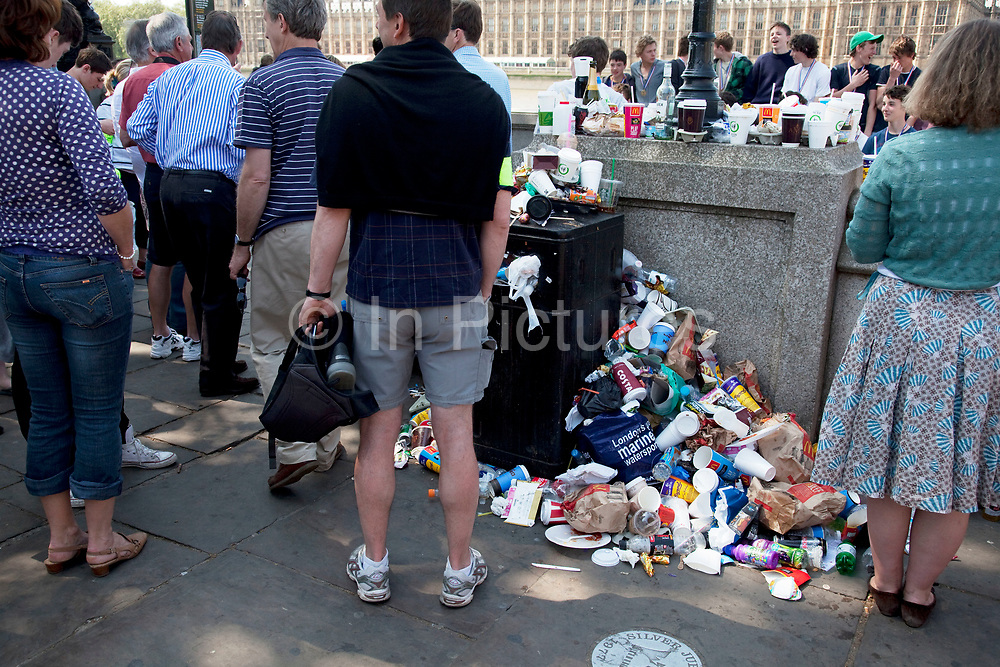 Overflowing bin and litter opposite the Houses of Parliament, central London. At certain times, especially weekends and public holidays, the volume of people in the area generates a big problem with trash. Rubbish piles high in certain places and proves unsightly for such an important area of London. Tourists gather her to take pictures. The result of so may people is plain to see.