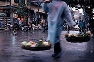 Street of Hanoi by a rainy day. On the foreground, a woman carries vegetable on her yoke. Motion and blur. Vietnam, Asia