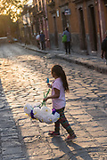 A young Mexican girl carries paper flowers and an ice pop at sunset during El Viernes de Dolores as part of Holy Week March 23, 2018 in San Miguel de Allende, Mexico. The event honors the sorrow of the Virgin Mary for the death of her son and is an annual tradition in central Mexico.