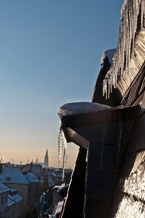 Deutschland,Köln Eiszapfen hängen glitzernd bei Sonnenaufgang an einem Schieferdach. Im Hintergrund der Kölner Dom  |  Iceicles hanging on a roof in Cologne, in the back the cathedrale  |