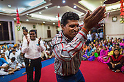 17 AUGUST 2014 - BANGKOK, THAILAND:  Men pray, sing and dance during Krishna Janmashtami observances at the Vishnu temple in Bangkok. Krishna Janmashtami is the annual celebration of the birth of the Hindu deity Krishna, the eighth avatar of the Hindu god Vishnu. It is celebrated by Hindus in Thailand. There are about 53,000 Hindus in Thailand, most originally from India, but many Hindu deities are highly revered by Thai Buddhists and Hindu holy days are observed by many Thai Buddhists.       PHOTO BY JACK KURTZ
