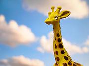 Toy giraffe on cloudy sky background