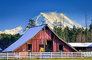Barn outside Mount Rainier National Park with the peak of the mountain looming behind it