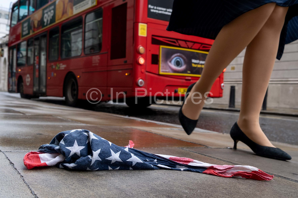 As a red London bus passes-by, a pair of legs walk past an American Stars and Stripes flag bandana lying on the wet pavement in the City of London, the UK capitals financial district, on 17th August 2020, in the City of London, England.