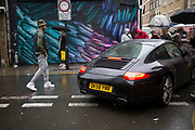 Wet day on Brick Lane in the East End of London, UK. Porche 911 drives through the market as people go about their day. It is an illustration of the haves and have nots as a sports car worth tens of thousands of pounds drives past stalls selling super cheap goods.