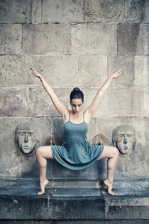 Ballet dancer dancing barefoot on a medieval fountain in the old quarter of Barcelona Spain