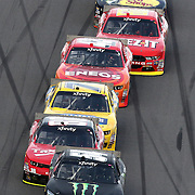 Kyle Busch (54) leads a pack of cars down the front stretch during the Alert Today Florida 300 XFinity Series race at Daytona International Speedway on Saturday, February 21, 2015 in Daytona Beach, Florida.  (AP Photo/Alex Menendez)