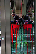 """Environmental Activist group Extinction Rebellion activists remain sat on the entrance doors of the bank Standard Chartered, which has been covered in red paint during an Extinction Rebellion climate change protest in the city of London on Friday, 27 Aug 2021. This is their fifth day of an ongoing two-week disruption protest campaign """"The Impossible Rebellion"""". (VX Photo/ Vudi Xhymshiti)"""