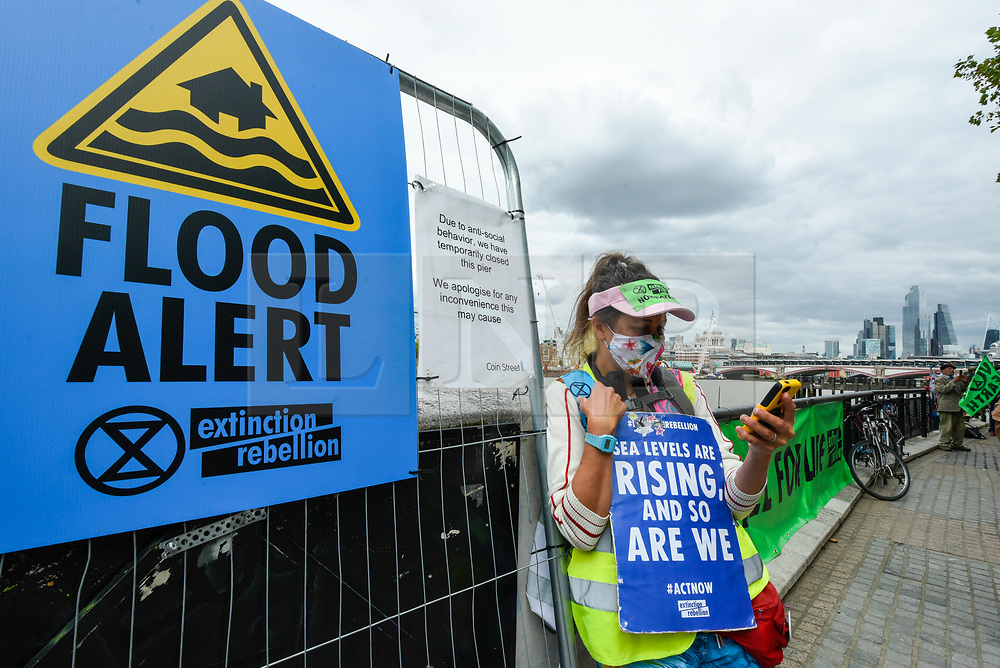 "© Licensed to London News Pictures. 06/09/2020. LONDON, UK.  An activist from Extinction Rebellion (XR) takes part in a ""Flood Alert"" protest on the shore of the River Thames near Gabriel's Wharf on the South Bank to highlight the effects of climate change on rising sea levels.  Photo credit: Stephen Chung/LNP"