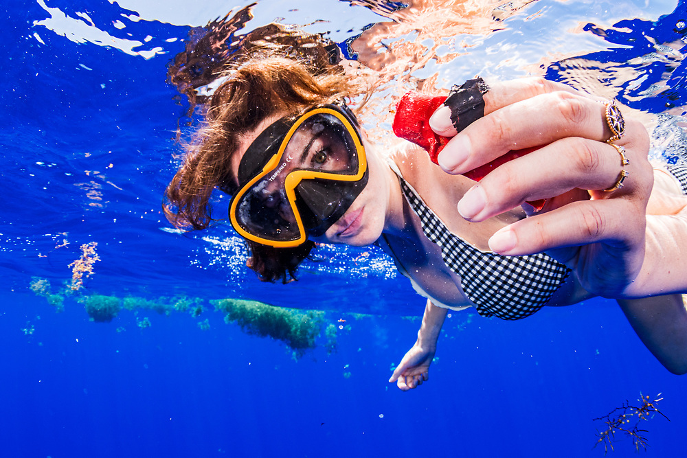 Actor and advocate Shailene Woodley finding and collecting plastic in the Sargasso Sea. In her hand we see a plastic shotgun shell in red and a piece of black garbage bag.