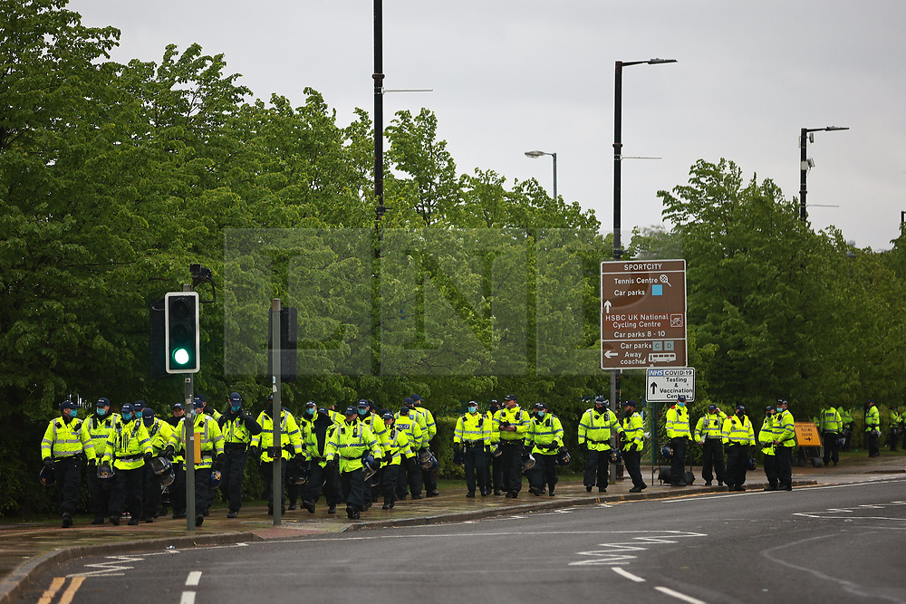 © Licensed to London News Pictures. 23/05/2021. Manchester, UK. Police and fans outside the stadium as the match ends. Manchester City fans are expected to celebrate outside the Etihad Stadium after their team beats Everton at home, having secured the Premiership title previously . Photo credit: Joel Goodman/LNP