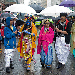 © licensed to London News Pictures. 12/06/2011. London, UK. A  girl with dressed as Krishna is sheltered from the rain during the Hare Krishna Ratha-yatra Festival of Chariots in London today (12/06/2011). 3 giant chariots are pulled from Hyde Park to Trafalger square accompanied by a procession of singers, musicians, and dancers. Rathayatra is celebrated by devotees of Lord Krishna all over the world. Photo credit should read: Ben Cawthra/LNP