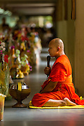 """12 JULY 2014 - PHRA PHUTTHABAT, SARABURI, THAILAND: A monk leads a chanting service before the Tak Bat Dok Mai at Wat Phra Phutthabat in Saraburi province of Thailand. Wat Phra Phutthabat is famous for the way it marks the beginning of Vassa, the three-month annual retreat observed by Theravada monks and nuns. The temple is highly revered in Thailand because it houses a footstep of the Buddha. On the first day of Vassa (or Buddhist Lent) people come to the temple to """"make merit"""" and present the monks there with dancing lady ginger flowers, which only bloom in the weeks leading up Vassa. They also present monks with candles and wash their feet. During Vassa, monks and nuns remain inside monasteries and temple grounds, devoting their time to intensive meditation and study. Laypeople support the monks by bringing food, candles and other offerings to temples. Laypeople also often observe Vassa by giving up something, such as smoking or eating meat. For this reason, westerners sometimes call Vassa """"Buddhist Lent.""""<br />     PHOTO BY JACK KURTZ"""