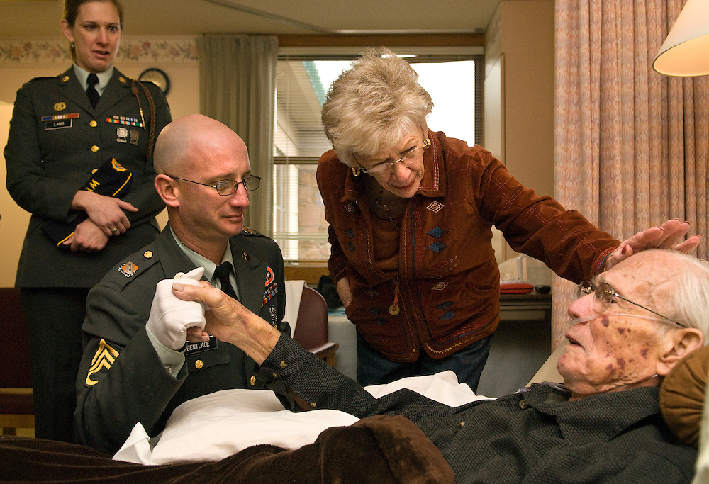 """Retired Air Force Capt. Gerald D. Binks lies in bed at St. John's Living Center with his wife Mary Lynn Yose Binks and American Legion Post 43 Commander David Bentlage at his side. The 87–year–old World War II veteran piloted B-17 bombers over Germany and was shot down and captured in 1944. Capt. Binks, originally from Casper, Wyo. suffers from congestive heart failure. """"It's time for me to go off to the happy hunting ground,"""" Binks said."""
