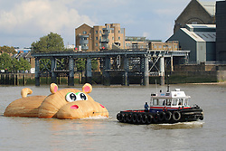© Licensed to London News Pictures. 02/09/2014. A wooden sculpture of a Hippo being towed up the Thames towards Battersea as part of the Totally Thames month long festival. The artist behind the sculpture is Florentijn Hofman. Hippo is seen here passing Greenwich including the Old Royal Naval College and Cutty Sark. Credit : Rob Powell/LNP