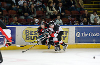 KELOWNA, CANADA, DECEMBER 3: Jordan Ktach #19 of the Prince George Cougars checks Colton Sissons #15 of the Kelowna Rockets into the boards as the Prince George Cougars visit the Kelowna Rockets  on December 3, 2011 at Prospera Place in Kelowna, British Columbia, Canada (Photo by Marissa Baecker/Shoot the Breeze) *** Local Caption ***