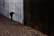 An orthodox Jewish male makes a bow for the night prayer in front of US-Mexico border on November 20th, 2018 at Friendship Park in Tijuana, Mexico.