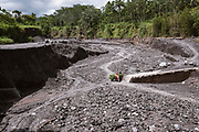 A local man rides with a load of grass down a lava flow used as a road after the 2010 Mt Merapi eruption in Java.