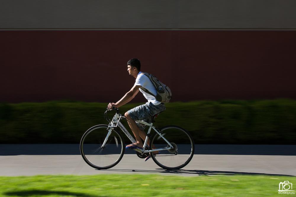 A student rides his bike near the Event Center at San Jose State University in San Jose, California, on August 22, 2014. (Stan Olszewski/SOSKIphoto)