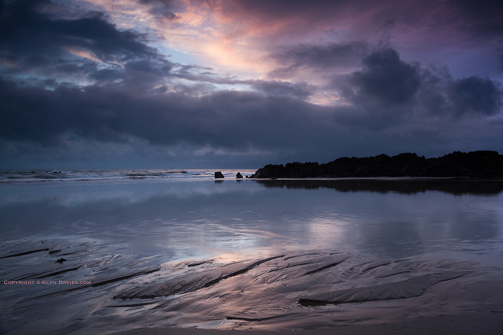 Showery weather forms dramatic skies and reflections at sunset on the wet sands of Porth Tyn Tywyn,  Rhosneigr, West Anglesey.