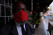 On a rainy night in Soho, security man 'H'  wears a bright red facial covering outside a business at a time when recently re-opened bars and restaurants are desperate for customer business during the coronavirus pandemic, on 27th August 2020, in London, England.