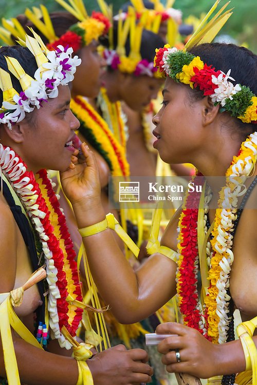 Yapese girls in traditional clothing helping to put on makeup at Yap Day Festival, Yap Island, Federated States of Micronesia