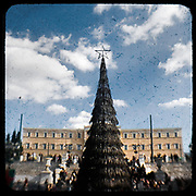 A burned Christmas tree in front of the Greek parliament in Syntagma Square. <br /> <br /> Following the murder of a 15 year old boy, Alexandros Grigoropoulos, by a policeman on 6 December 2008 widespread riots, protests and unrest followed lasting for several weeks and spreading beyond the capital and even overseas<br /> <br /> When I walked in the streets of my town the day after the riots I instantly forgot the image I had about Athens, that of a bustling, peaceful, energetic metropolis and in my mind came the old photographs from WWII, the civil war and the students uprising against the dictatorship. <br /> <br /> Thus I decided not to turn my digital camera straight to the destroyed buildings but to photograph through an old camera that worked as a filter, a barrier between me and the city.